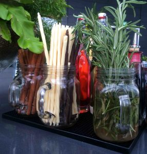 Rosemary, white chocolate, dark chocolate, and cinnamon drink garnishes in glass mugs for storage.