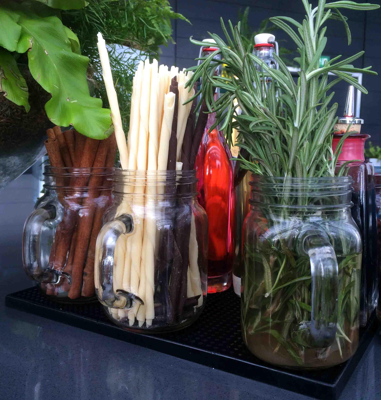 Rosemary, white chocolate, dark chocolate, and cinnamon drink garnishes in glass mugs for storage.
